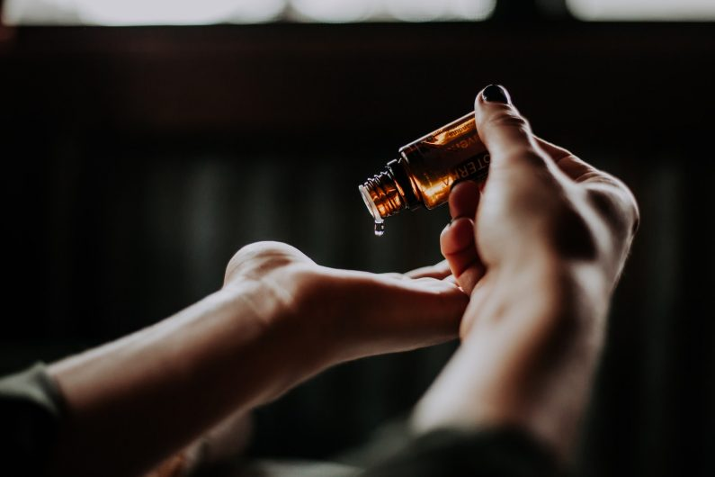 a women pouring essential oil in her hand