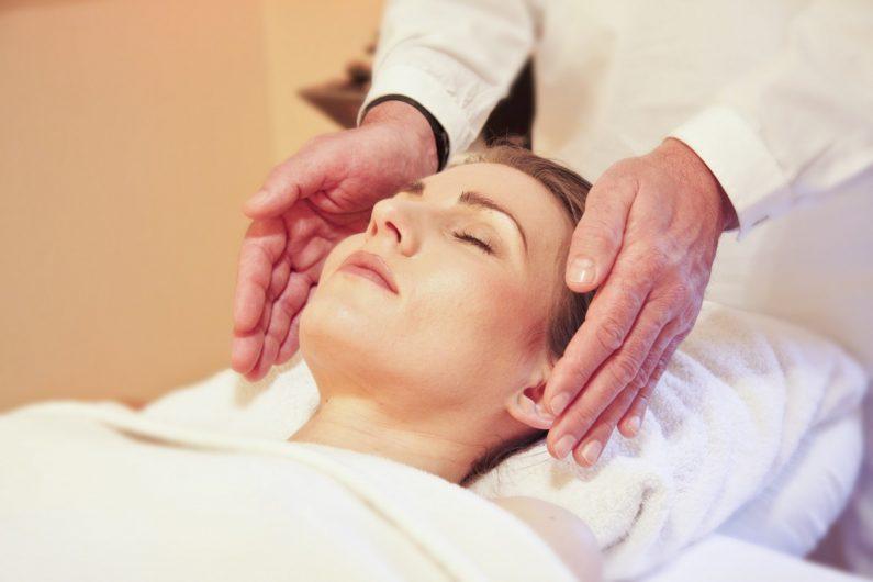 demonstrating reiki massage; a woman laying on a table with a mans hands hovering around her head